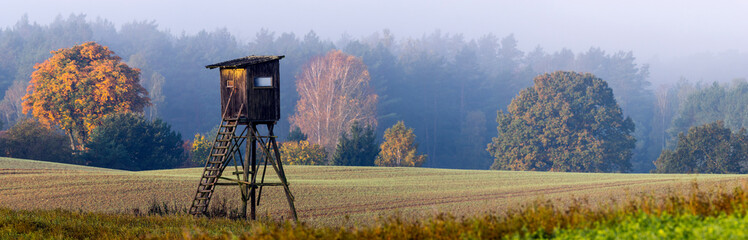 Hunting tower on the edge of the forest during a beautiful sunrise on a foggy morning