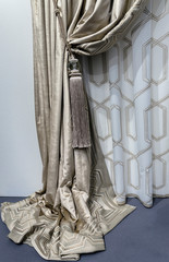 Fragment of the beige velvet curtains with embroidery and a luxurious brush