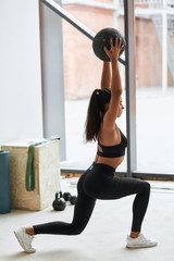 Young caucasian woman in black topic and leggins do exercises with black fitness ball in gym....