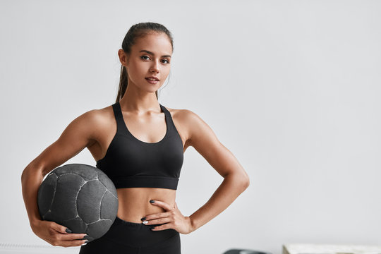 Sportive caucasian cross fit woman with fitness ball stand in gym, look at camera. White wall background