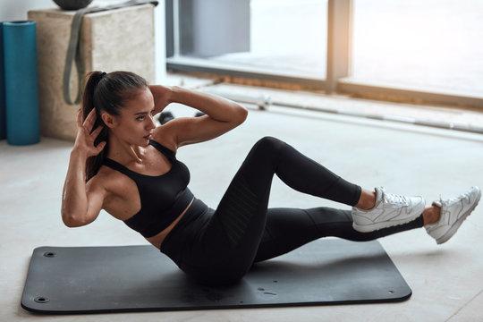 Slim sporty girl in sportswear pumping press lying on mat in gym. Window background
