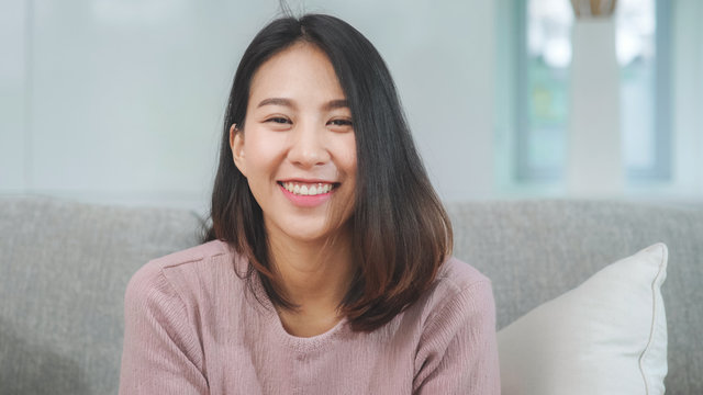 Teenager Asian woman feeling happy smiling and looking to camera while relax in living room at home. Lifestyle beautiful Asian young female using relax time at home concept.