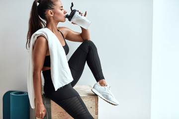 Attractive slim female drinking water and having rest after fitness, pilates. White towel in shoulders