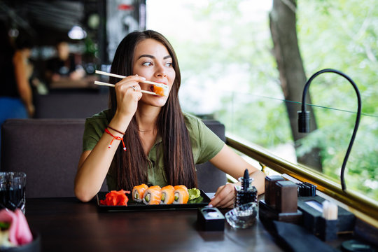 Young woman eating and enjoying fresh sushi in luxury restaurant. Female client holding food sticks and eating oriental meal on lunch. Concept of food.