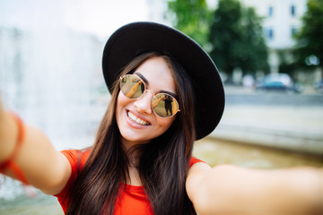 Young woman in hat and sunglasses taking selfie photo near fountain outdoors