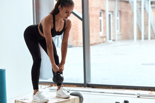 Fit caucasian woman with dumbbells training in gym, doing squats. Cross fit, healthy lifestyle