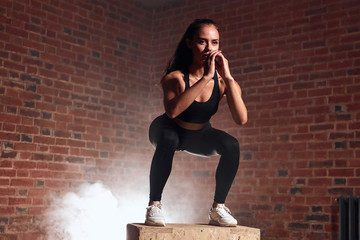 Slim sport woman in sportswear jumping on fit box and do squats. Crossfit, bodybuilding. Brickwall...