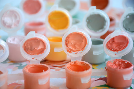 Small jars filled with paint on a painted canvas. Painting by numbers. Bright and colorful. Creative hobby. Crafts and DIY