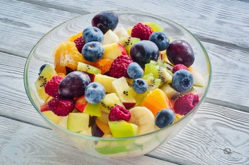 Fresh colorful fruit. Salad of various fruits on a wooden kitchen table.
