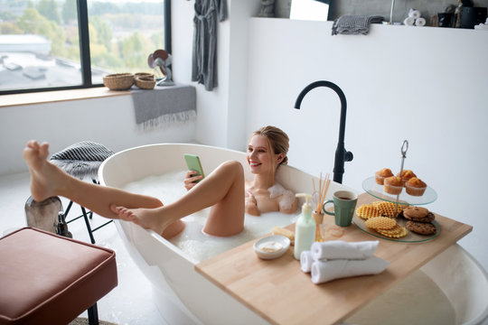Woman having breakfast and using phone while lying in bath