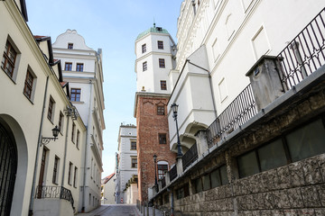 Narrow street between old houses and the Ducal Castle in Szczecin, Poland, former seat of the dukes of Pomerania-Stettin, blue sky