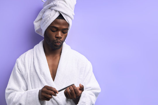 Cool handsome man in bathrobe doing manicure for himself with nail file isolated ober purple background