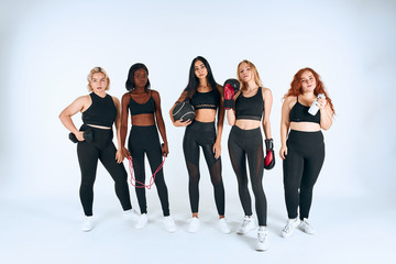 Young different girls in sportive wearing posing, look at camera, holding boxing gloves, dumbbells, sportive things