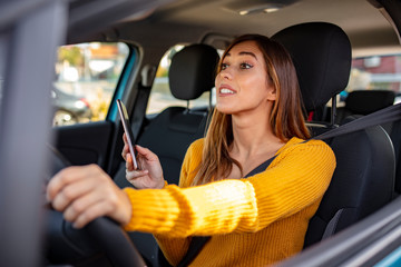 Texting and driving, behind the wheel. Breaking the law. Woman driving car distracted by her mobile phone. Woman typing message on the phone while waiting in the car.