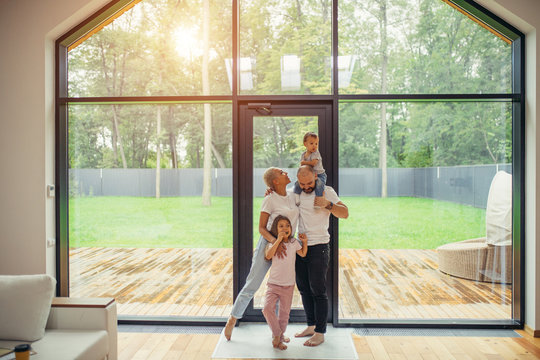 Beautiful and happy family together at home with panoramic window standing. Baby sit at daddy's head. Hug each other