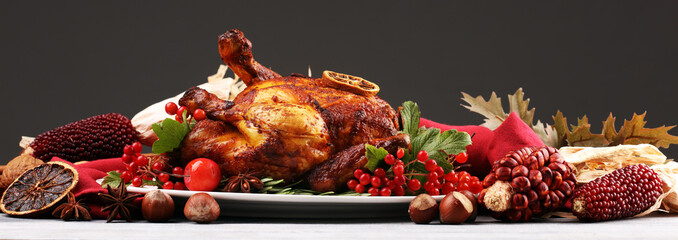 Baked turkey or chicken. The Christmas table is served with a turkey, decorated with fruits, salad and nuts. Fried chicken, table. Christmas