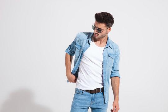 Young fashion man holding adjusting his jacket