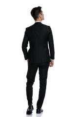 back view of young elegant man in tuxedo looking up