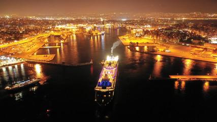 Aerial drone night shot of beautiful illuminated port of Piraeus and huge cruise liner departing to Aegean popular destinations, Attica, Greece Fototapete