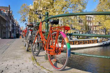 Fotorolgordijn Fiets Orange bike with LGBT flag parked on a bridge in Amsterdam, Netherlands
