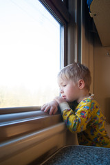 A bright, cute three-year-old boy riding a train looks out the window, behind which a dull landscape sweeps through. Vertical photo.