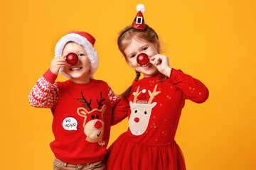 happy funny emotional children boy and  girl in red Christmas reindeer costume  on yellow   background.