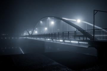 łuki nowoczesnego mostu we mgle w nocy