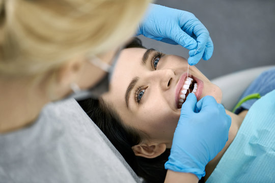 Pretty woman's teeth cleaning in dental clinic