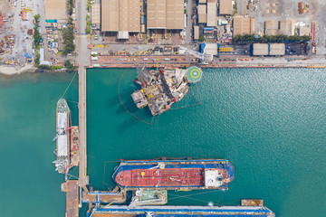 Wall Mural - Aerial view of a jack up oil drilling rig and dry dock ship in the shipyard for maintenance