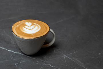 one cup of coffee stands on a granite table, latte art on foam
