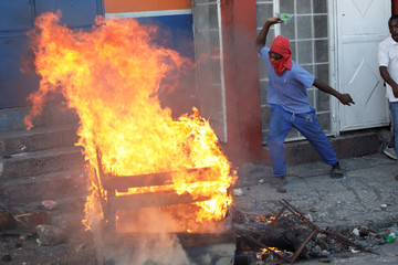 A man throws a plastic bag to a fire where a dead body is burning, in the streets of Petion Ville, Port-au-Prince