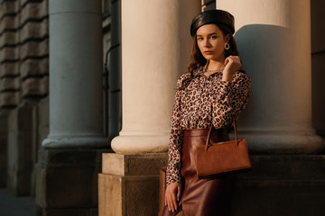 Outdoor fashion portrait of young elegant luxury woman wearing leopard print shirt, faux leather skirt, beret, holding small brown classic bag, handbag, posing in street Copy, empty space for text  Wall mural