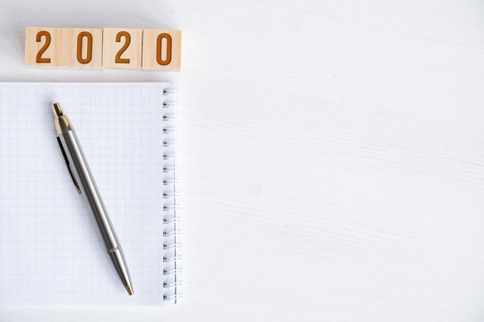 Blank spiral notebook, pen, wooden cubes with numbers new year 2020 with copy space.