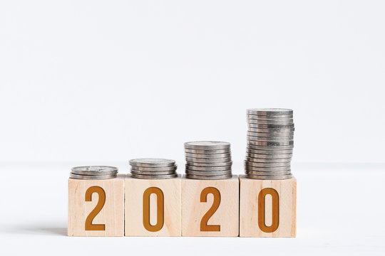 Stacks of coins on cubes with numbers 2020. Concept of saving in new year.