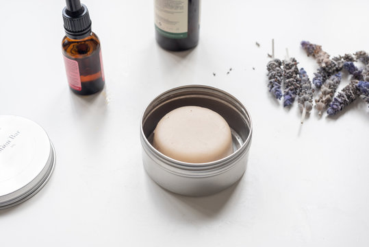 Closeup of lotion bar in silver tin on white table with lavender and oils - natural wellness concept (selective focus)