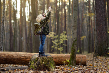Little boy scout with spyglass during hiking in autumn forest. Child is looking through a spyglass.