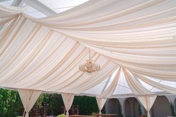 Stunning wedding venue with white canopy and curtains under the glass roof