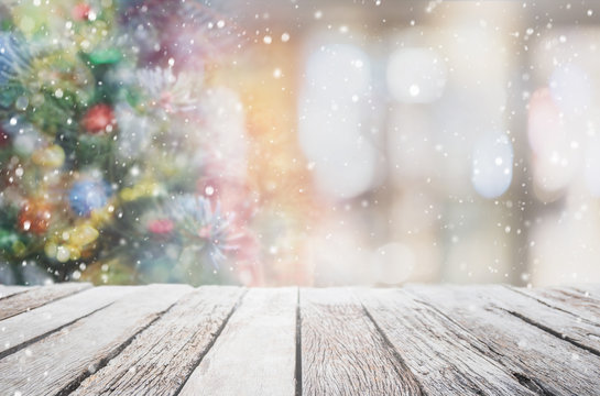 Empty wood table top on blur with bokeh Christmas tree and new's year decoration on window background with snowfall - can be used for display or montage your products.