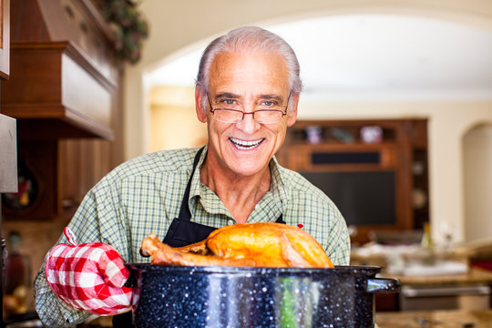 Good looking senior man holding turkey