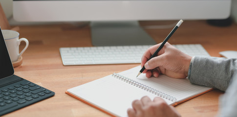 Cropped shot of professional businessman writing his idea on notebook