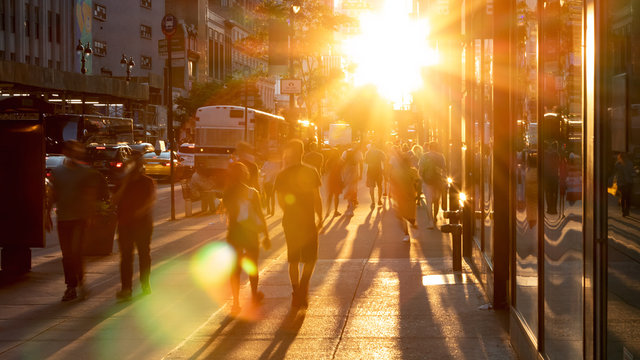 Sunlight shines on the diverse crowds of people walking down the busy sidewalk on 34th Street through Midtown Manhattan in New York City