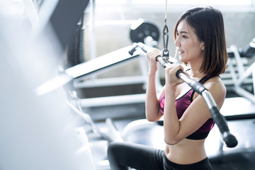 Asia woman exercise with exercise machine cable in gym.