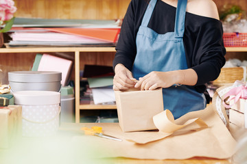 Cropped image of flower shop worker in blue apron wrapping gift box in decorative paper