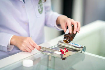Pharmacist separate and count medicine capsule in steel tray by hand