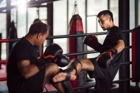 Asian kickboxing player and him trainer in boxing gym