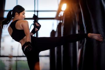 Asian girl kick a sand bag in kickboxing gym