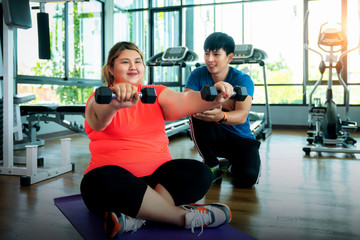 Asian fat girl work out and weight lifting with her trainer