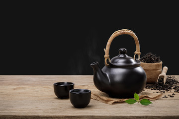 Cup of hot tea with teapot, green tea leaves and dried herbs on the wooden table isolate black background with empty space, Organic product from the nature for healthy with traditional