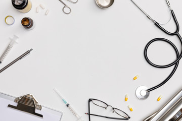 Creative flatlay of doctor medical equipment white table with stethoscope, medical documents, thermometer, syringe and pills, Health care concept, Top view with copy space, Isolated on white