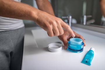 Man applying cream morning skincare regimen moisturizing face skin at bathroom mirror. Male beauty men skin care closeup of product jar and finger putting lotion.